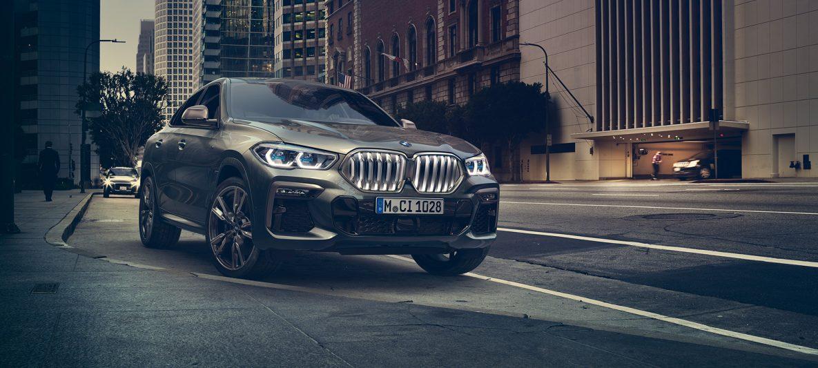 BMW X6 M50i in Dreiviertel-Frontperspektive stehend vor urbaner Kulisse